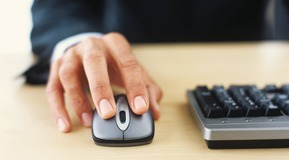 Mans hand on computer mouse.