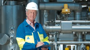 -Linde employee with a clipboard in front of production plant